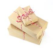 Pacote do papel de Brown amarrado com corda vermelha e branca no backg branco Fotografia de Stock Royalty Free