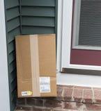Pacote entregado à porta traseira da casa imagens de stock royalty free