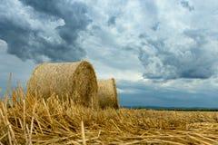 Pacotes da palha em nuvens de tempestade da terra Fotos de Stock Royalty Free