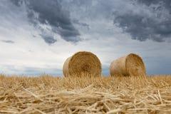 Pacotes da palha em nuvens de tempestade da terra Fotos de Stock