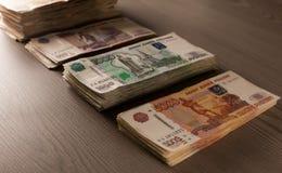 Pacotes de dinheiro Rublos de russo em um fundo de madeira Fotografia de Stock