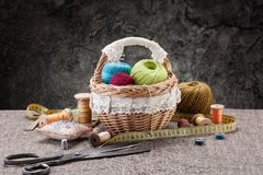 Pacotes de linha na cesta, nas tesouras e na linha nos cilindros sobre Foto de Stock