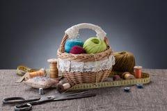 Pacotes de linha na cesta, nas tesouras e na linha nos cilindros sobre Fotografia de Stock
