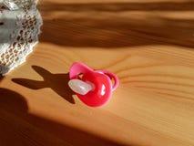 Pacyfikator czerwień na drewnianym stole obrazy stock