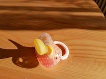Pacyfikator czerwień na drewnianym stole zdjęcia royalty free