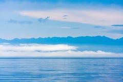 Pacyfikujący mgłę nad jeziorem z niskimi chmurami i halnymi sylwetkami, zdjęcia royalty free