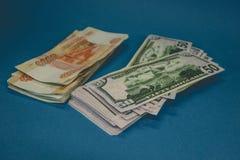 paczka Rosyjscy ruble i dolary dwa zwitka pieni?dze na b??kitnym tle bogactwo sposobno?? sukces obrazy royalty free