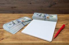 Paczki sto dolarów, notatnik i pióro, kłamają na textured drewnianym stole obrazy royalty free