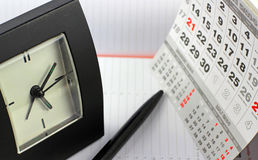 Pad, clock  on calendar sheets Royalty Free Stock Photo