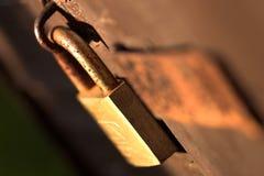 Pad Lock Rust Rusty Close up old worn. Depth of Field Orange Red Colour Safe Secure Sunlight Latch Key Screws Metal Security Stock Photo