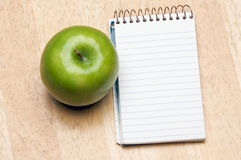 Pad of Paper and Apple on Wood Royalty Free Stock Images
