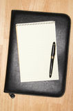 Pad of Paper, Pen & Binder. Pad of Paper, Pen & Leather Binder on a wooden background Royalty Free Stock Image