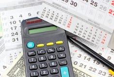 Pad, pencil, calculator  on calendar sheets Royalty Free Stock Photography