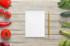 Pad and pencil for writing a vegetarian list of ingredients. Empty paper for text royalty free stock images