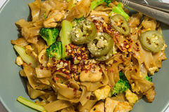 Pad See Ew Noodle. Flat rice noodle stir fry wtih chicken, egg broccoli top with crushed red pepper and green chilli in the vinegar. Thai style Royalty Free Stock Images