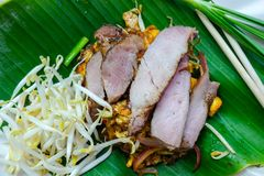 Pad Thai. Famous traditional Thai food. Stir-fries noodle with pieces of pork on top. Decoration with plate that made from. Tropical banana leaf. Copy space stock image
