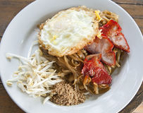 Pad Thai Noodles with Eggs and Pork. A traditional dish of Pad Thai noodles served with a fried egg, grilled pork and bean sprouts Royalty Free Stock Images