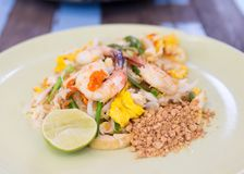 Pad thai, Thai food stir fry noodles with shrimp, vegetable and. Peanuts in plate on wooden table in the restaurant stock image
