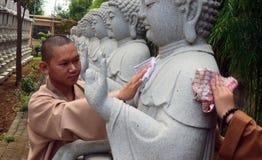 Pada Hari Waisak för bersih för Biksu membersihkan patungBuddha Royaltyfri Fotografi