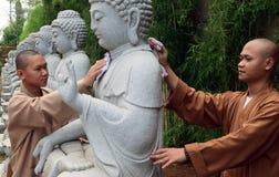 Pada Hari Waisak för bersih för Biksu membersihkan patungBuddha Royaltyfri Bild