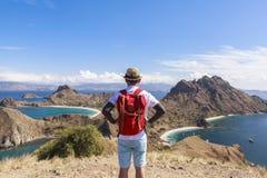PADAR海岛的,科莫多国家公园,印度尼西亚一个背包徒步旅行者 免版税库存照片