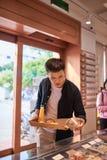 Padaria de compra do homem asi?tico consider?vel para a ruptura de caf? na tarde Ruptura da padaria e de caf? imagem de stock