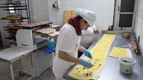 Padaria italiana tradicional Dois padeiros fêmeas preparam bolos doces com Pasticcera de creme, passas e maçãs video estoque