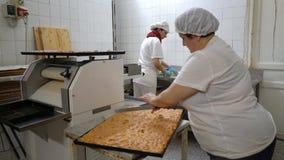 Padaria italiana tradicional Um padeiro fêmea corta uma torta grande em partes filme