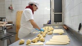 Padaria italiana tradicional Um padeiro fêmea gerencie croissant bonitos antes de cozer video estoque