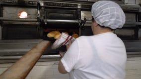 Padaria italiana tradicional Um padeiro fêmea toma bolos quentes fora do forno vídeos de arquivo