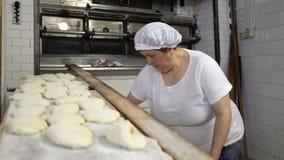 Padaria tradicional do italiano da família Um padeiro da mulher prepara o pão cozendo video estoque