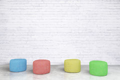 Padded stools in brick room Royalty Free Stock Images