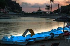 Paddel-Boote eins mit Dia werden entlang Küstenlinie stationiert Einrichtungen und Bäume auf dem Hintergrund Rötlicher Gray Sky stockbilder