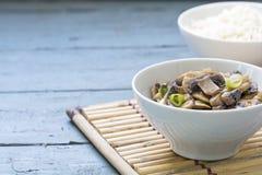 Paddestoel plantaardige schotel en gekookte rijst in witte kommen op een bamb Royalty-vrije Stock Foto's