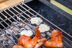 Paddestoelen met kaas en kippenvleugels bij de barbecuegrill op hete houtskool en brand Stock Afbeelding