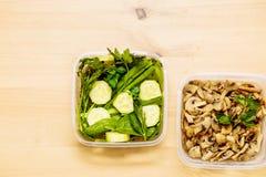 Paddestoelen, verse kruidendille, peterselie, uien, spinazie en besnoeiingsstukken komkommers op twee containers op de keukenlijs royalty-vrije stock afbeeldingen