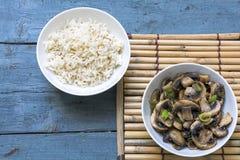Paddestoelgroenten en gekookte rijst in kommen op een bamboemat en Royalty-vrije Stock Foto