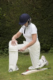 Padding up Lady cricketer putting on leg pads. Elderly female cricketer fastens leg pads before going into bat stock photo