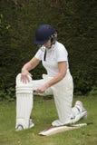 Padding up Lady cricketer putting on leg pads Stock Photo