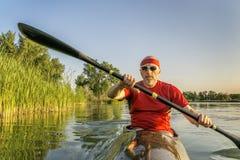 Paddla den tävlings- havskajaken på sjön Arkivfoto