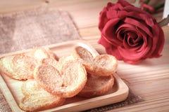 Paddla en fjäril, den hjärta formade lilla pastejen som är frasig med socker i en träplatta Royaltyfri Foto