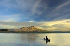 Paddla en kanot i soluppgången arkivbild