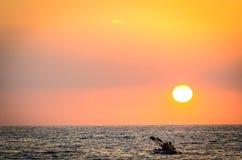 Paddla in i solnedgången Arkivbild