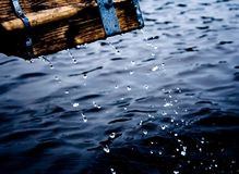 Paddle. Wooden paddle with frozen waterdrops falling down over a dark blue water royalty free stock images