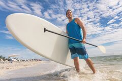 Free Paddle Board Fun SUP Watersport Fitness Man Carrying Paddleboard After Water Surf Session In Sanibel Island, Florida Stock Images - 194172584