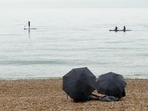 Paddle board and kayaks on sea with two umbrellas in the foreground Stock Image