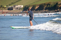 Paddle boarder. Surfing on wave royalty free stock photo