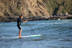 Paddle boarder. Stand up paddle boarder in waves stock photos