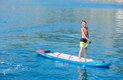 Paddle boarder. Child boy paddling on stand up paddleboard. Healthy lifestyle. Water sport, SUP surfing tour. In adventure camp on active family summer beach royalty free stock images