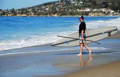 Paddle boarder entering water in Laguna Beach, California. Stock Images
